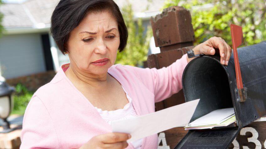 Worried Senior Hispanic Woman Checking Mailbox.