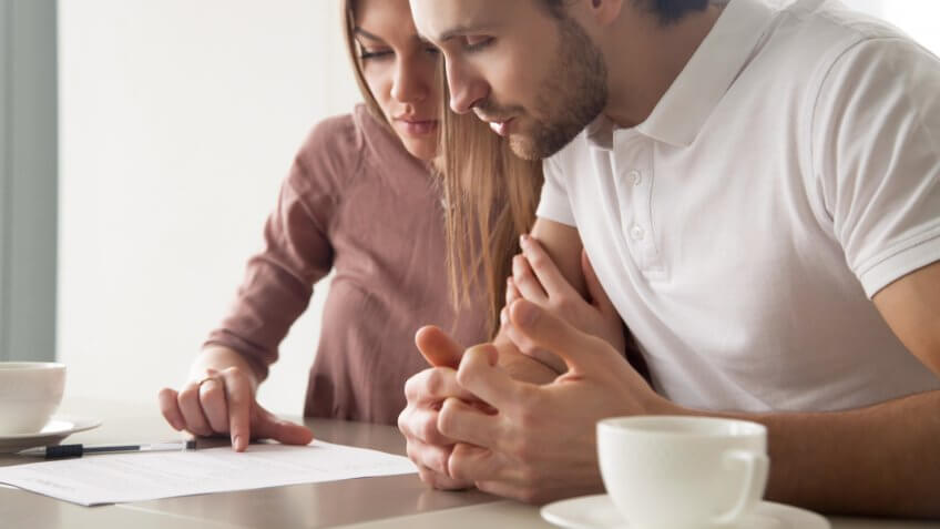 Serious couple studying contract agreement, reading terms and conditions attentively before signing, husband and wife calculating domestic bills, considering mortgage loan offer, health insurance.