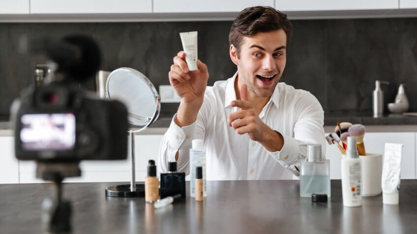 Handsome young man filming his video blog episode about new cosmetic products while sitting at the kitchen table and pointing finger.