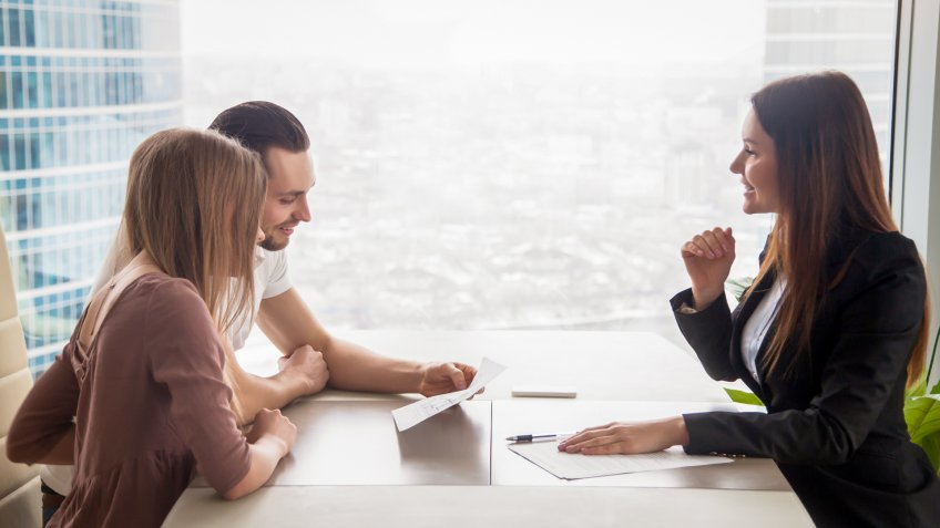 Side view of realtor and young couple sitting at office desk discussing property for sale.