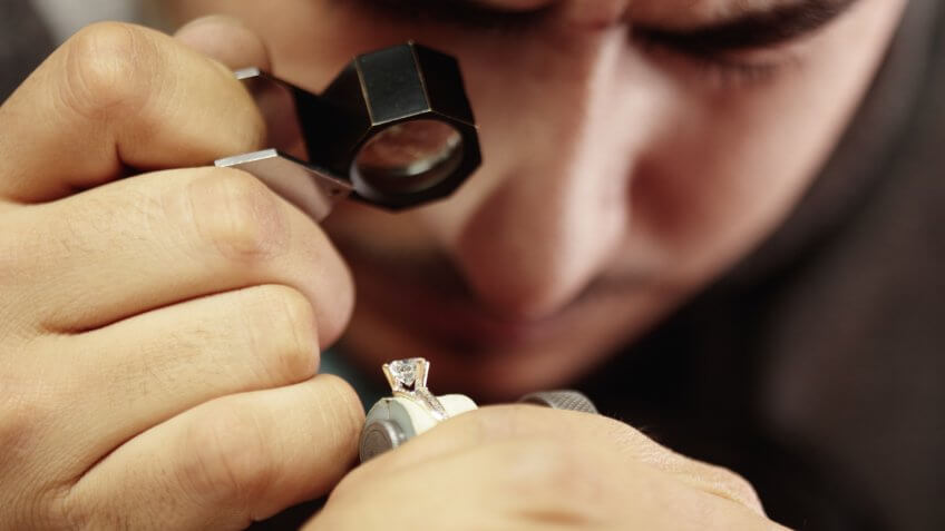 Jeweler repairing diamond ring in workshop.