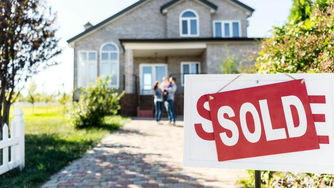 sold house with blurred family on background.