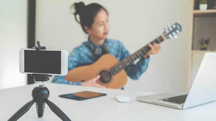 Young female blogger with smartphone recording video at home.