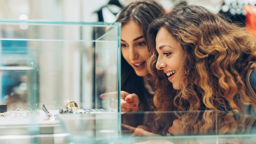 Close-up of two young women looking at expensive jewelry in the fashion store.