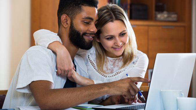 Young couple filling forms of banking application in domestic interior.