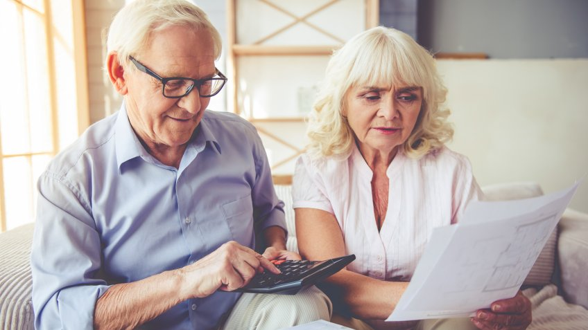 Handsome old man and beautiful woman are examining documents, using calculator and smiling while sitting on couch at home.