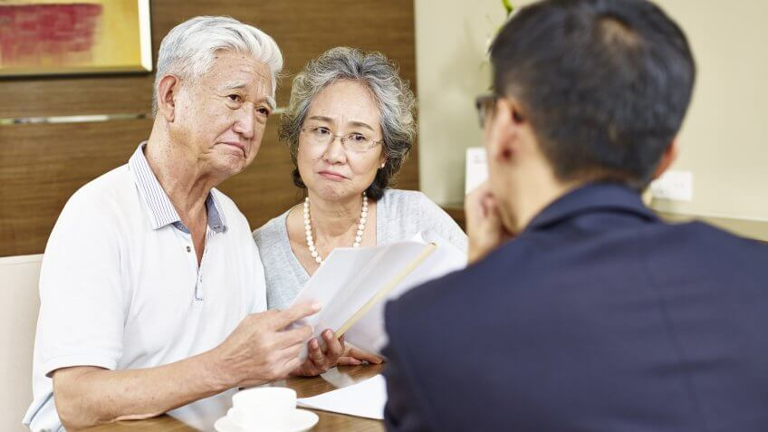 elderly couple talking to financial expert