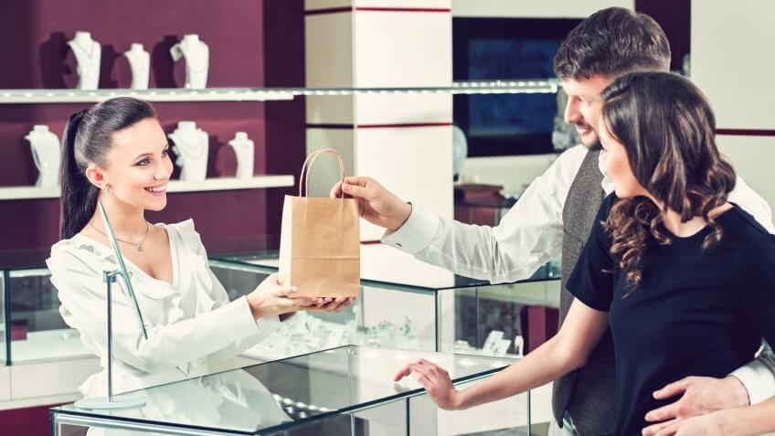 Cheerful female jeweler handing purchase in a shopping bag to he.