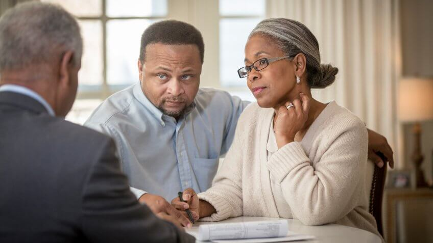 African American couple talking to businessman.