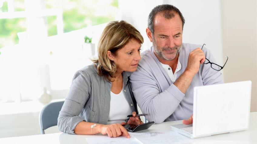 Couple reading construction plan at home with use of laptop.
