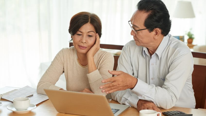 Unhappy Vietnamese senior couple discussing family budget.