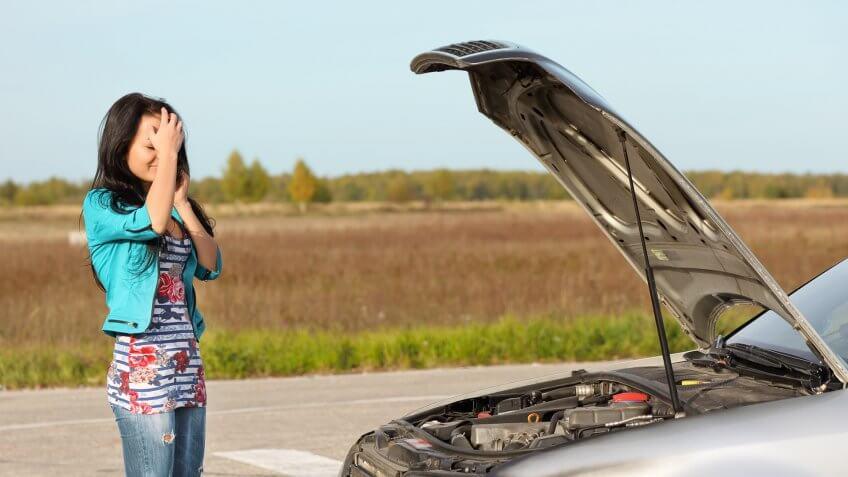 attractive-brunette-front-her-car-broken