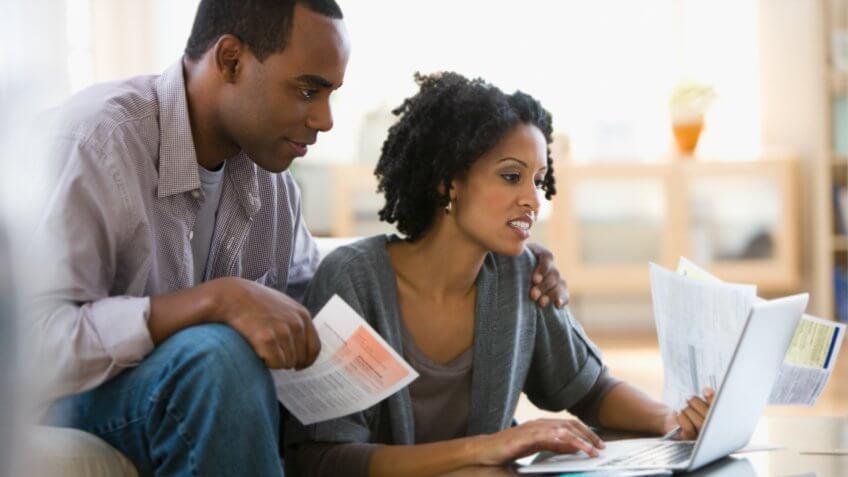 Couple paying bills using laptop.