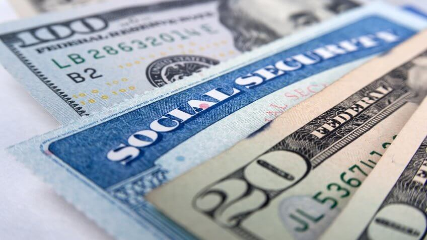 Social security card and American money dollar bills close up concept.