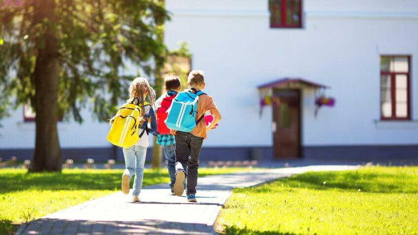 Children with rucksacks running in the park near school.