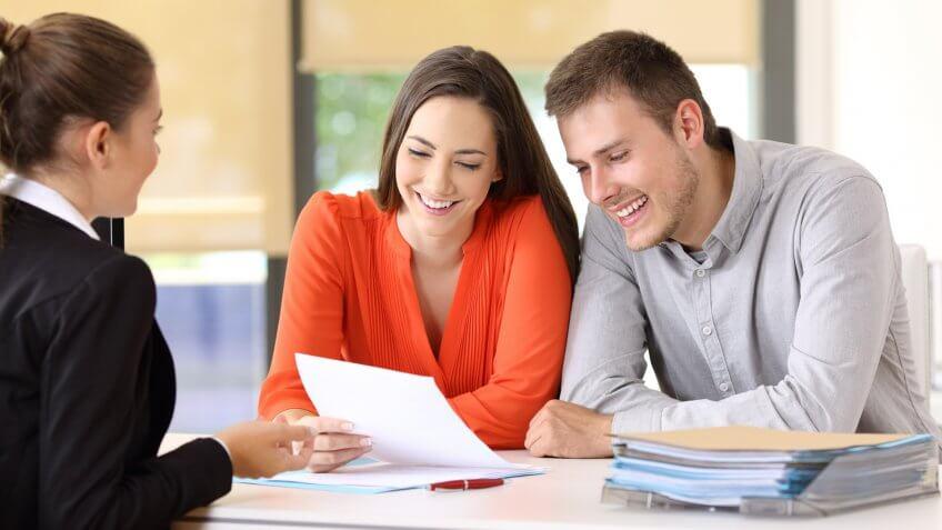 saleswoman-talking-couple-happy-customers