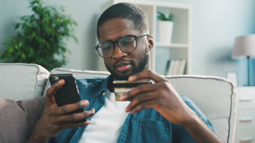 African young man in glasses shopping online with credit card using smart phone at home.