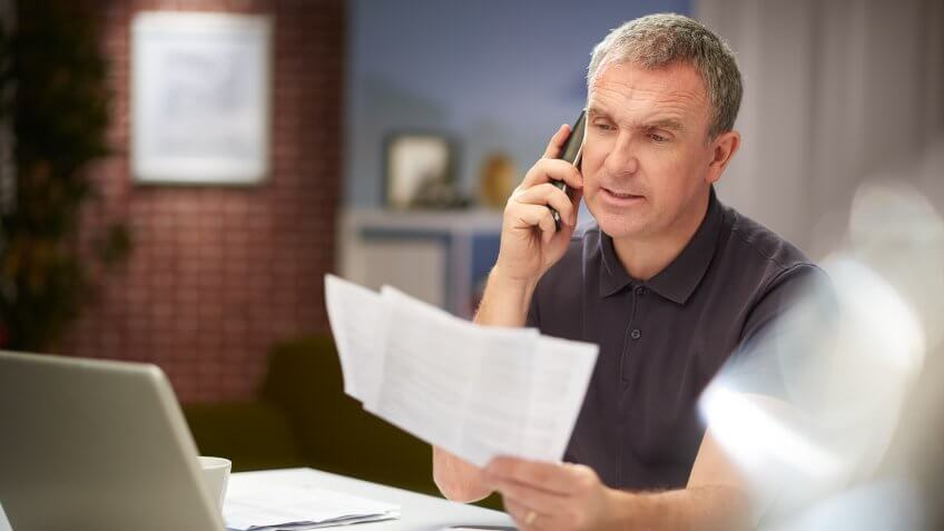 a mature man sits at his dining table at home looking through some bills and paperwork , whilst chatting on the phone .