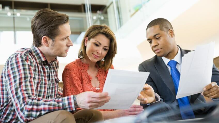Couple reviewing paperwork with financial advisor.