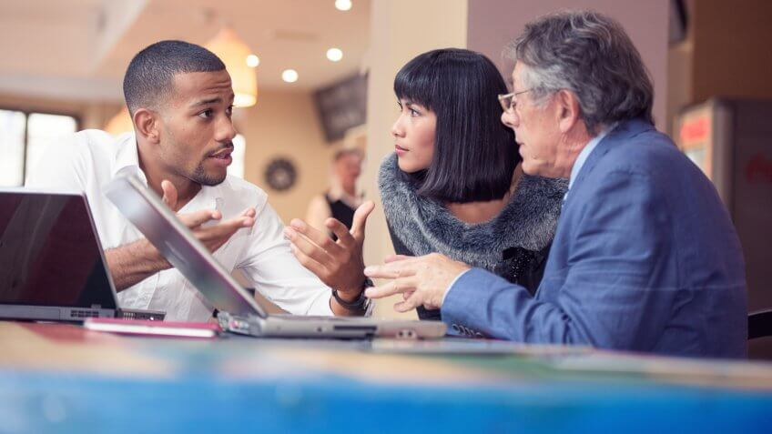 Three people talking business in a relaxed bar environment.