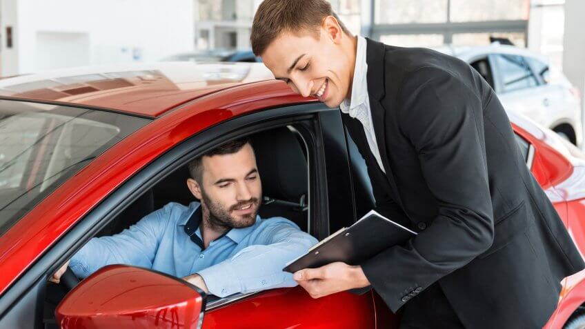 Photo of young male consultant and buyer signing contract for new car in auto show.