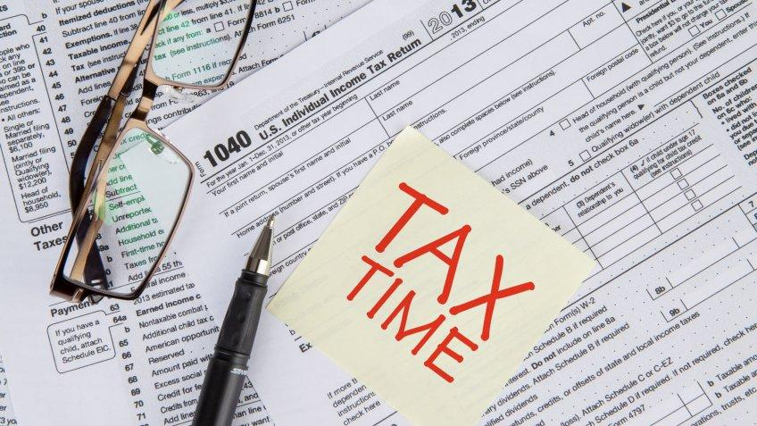 CLoseup of a text of tax time on the paper note with tax form, glasses, and pen.