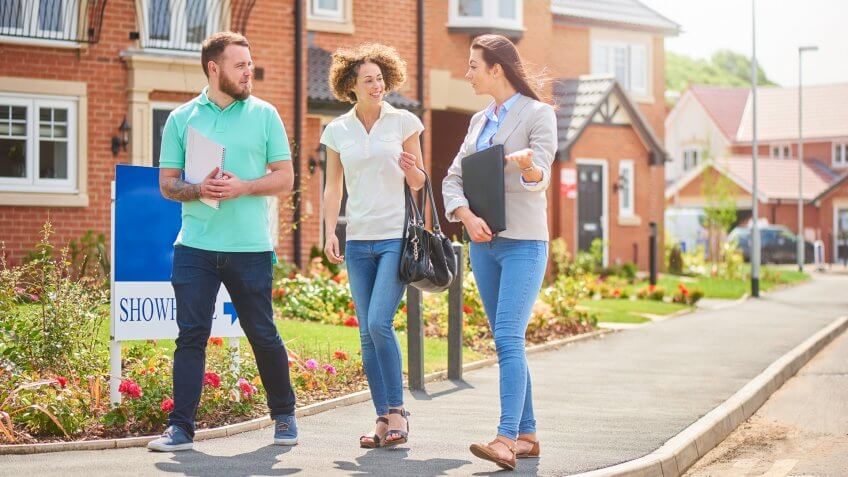 a mid adult couple browse a new housing development whilst listening to the sales assistant or estate agent  .