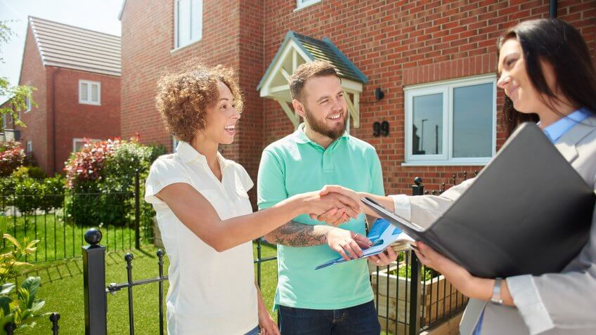 a mid adult couple celebrate receive the keys to their new house from the estate agent  .