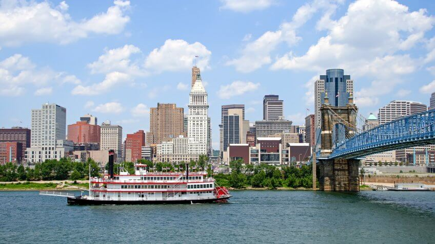 Replica steamboat travels down the Ohio River in front of the Cincinnati skyline.