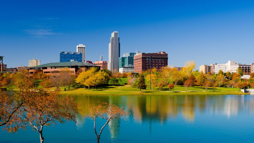 Downtown Omaha skyline with the Heartland of America Park (with a lake and fall colored trees) in the foreground.