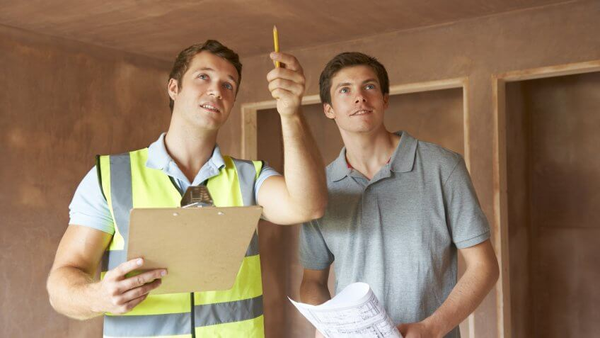 Builder And Inspector Looking At New Property.