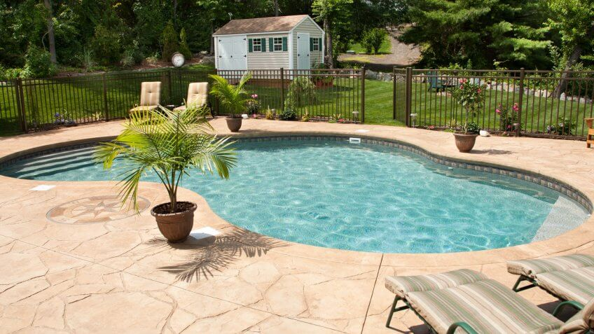 """Lush, resort-like backyard salt water swimming pool with flagstone stamped concrete patio."