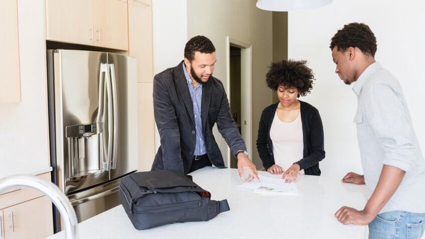 Couple talking to broker in new house.