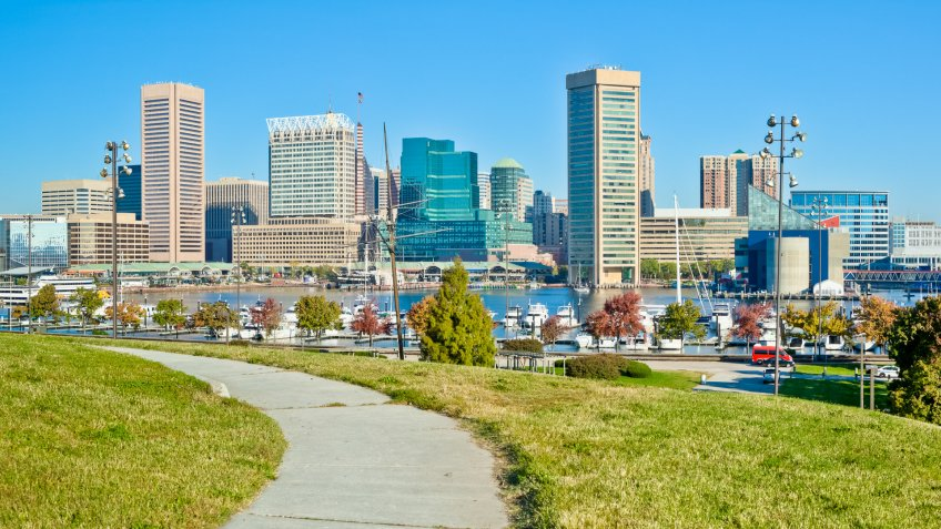 Panoramic image of Baltimore's Federal Hill, overlooking the Inner Harbor and its many tall buildings on a sunny autumn afternoon under a clear blue sky.