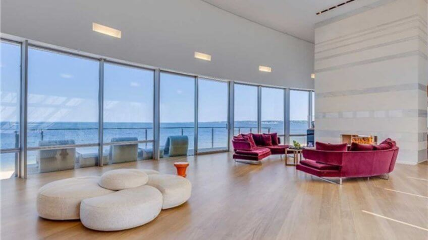 open living room space facing a wall of windows that overlook the beach
