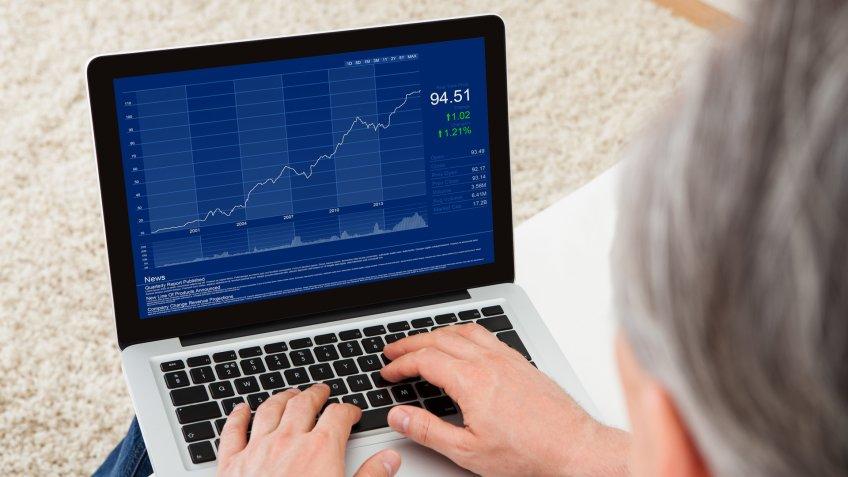 Close-up of mature man looking at stock charts.