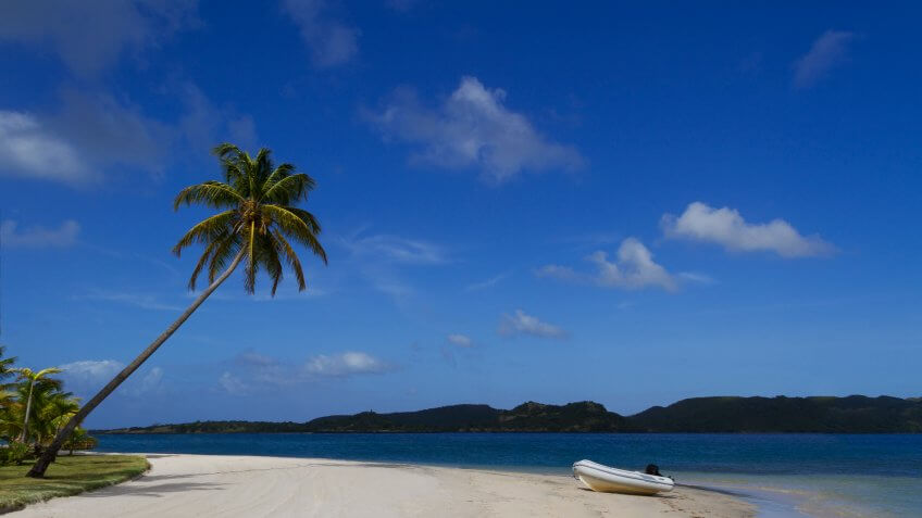 Dingy on shore of beautiful tropical sandy beach at Calivigny Island, Grenada in the Caribbean.