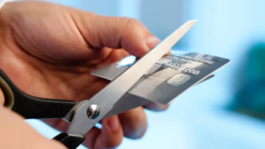 Scissors cutting a credit card on blue background.