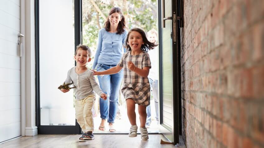 Excited Children Arriving Home With Parents.