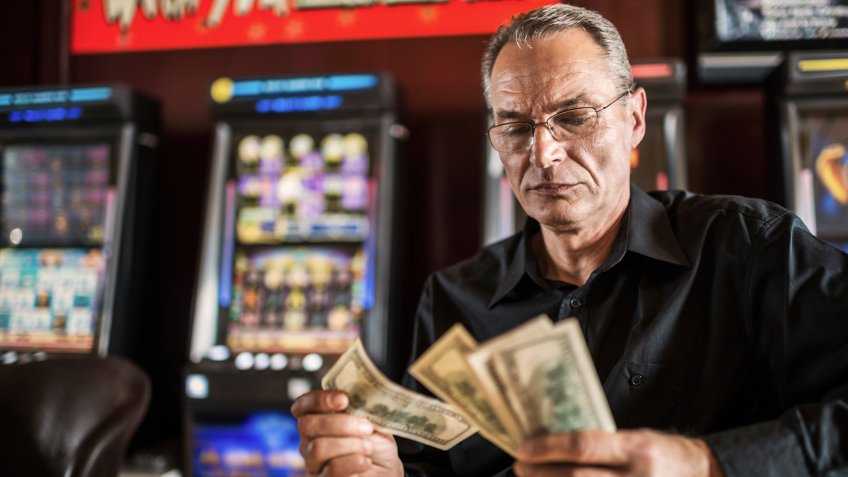 Mature man counting dollars he had won in a casino.