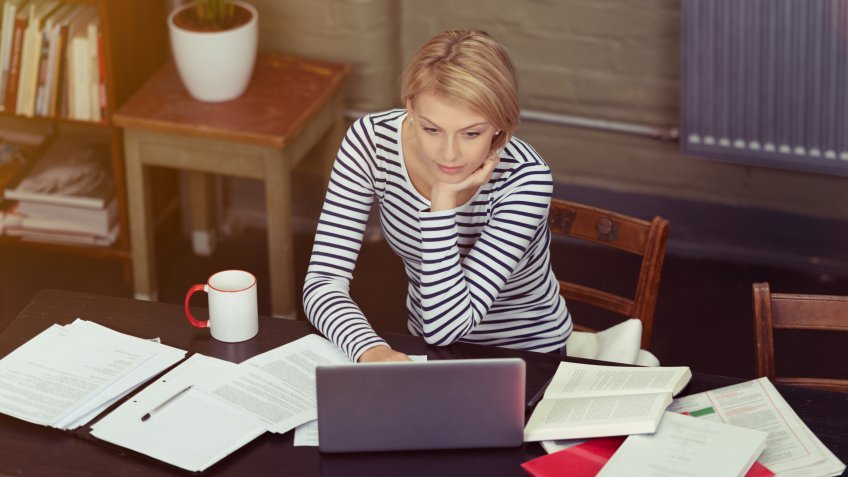 Attractive businesswoman surrounded by paperwork as she sits at her desk working on a laptop computer, high angle view.