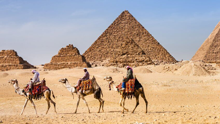 Bedouins raiding on camels, pyramids on the background, Giza, Egypt.