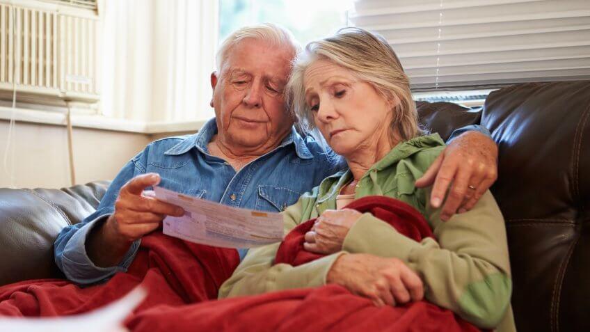 Worried Senior Couple Sitting On Sofa Looking At Bills Under A Blanket.