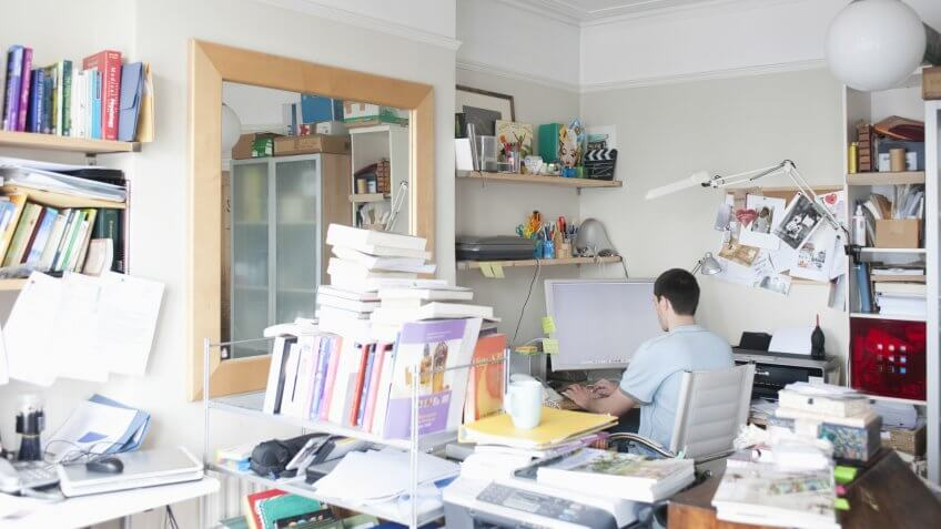 Rear view of businessman using computer in creative office space.