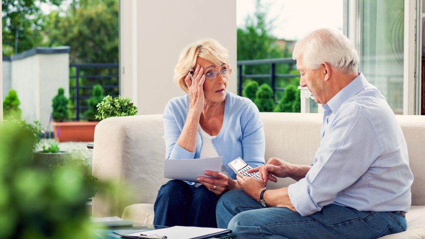 Worried senior couple sitting on sofa at home and looking over bills.