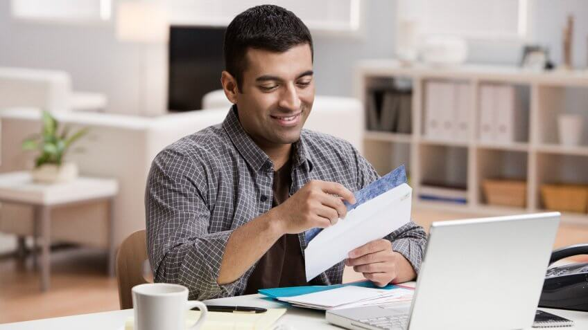 Hispanic man opening mail in home office.