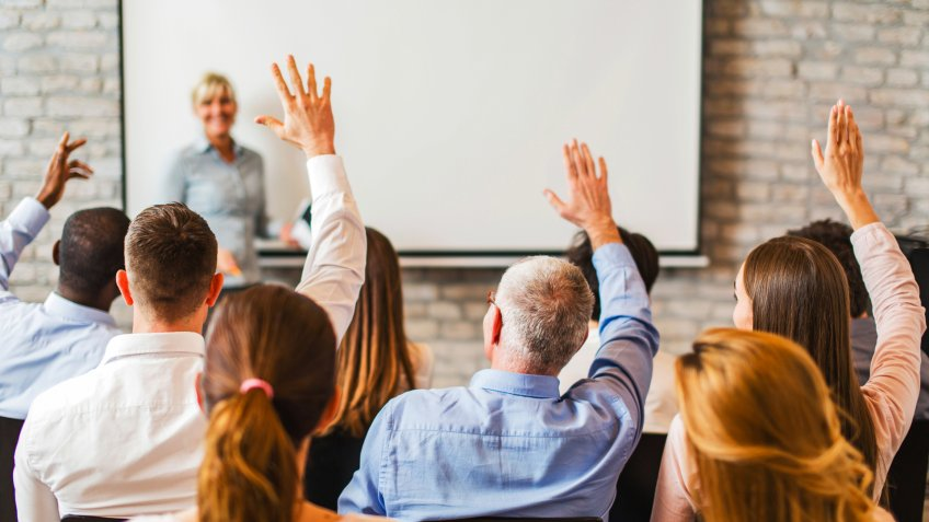 Rear view of group of business people at a lecture raising their hand ready to answer the question.