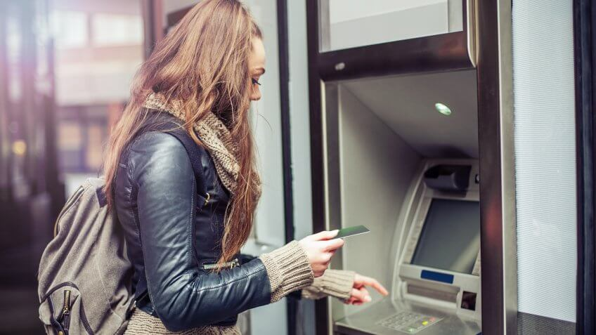 Young woman withdrawing money from credit card at ATM.