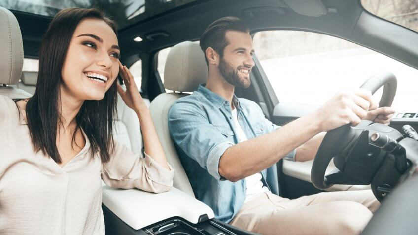 Beautiful young couple sitting on the front passenger seats and smiling while handsome man driving a car.