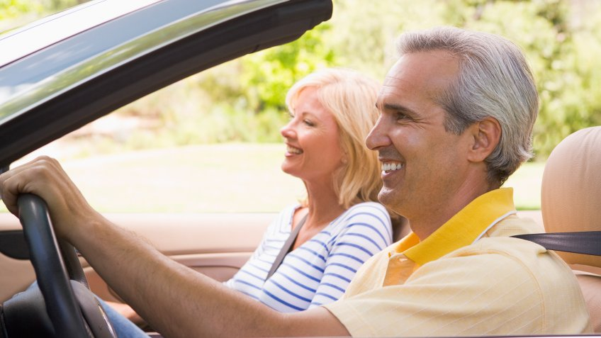 Couple driving in convertible car with top down smiling.